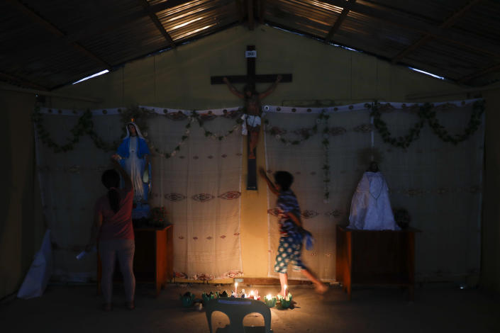 Residents who used to live at Taal volcano pray at their chapel at a relocation site in Balete, Batangas province, Philippines, Sunday, Jan. 10, 2021. Some families are still living in tents and have resorted to taking odd jobs to make a living as the government has prevented them from returning back to their homes almost a year after Taal volcano erupted. Taal erupted on Jan. 12, 2020. The eruption displaced thousands of villagers living near the area and delivered an early crisis this year for one of the world's most disaster-prone nations a couple of months before the COVID-19 pandemic broke in the country. (AP Photo/Aaron Favila)