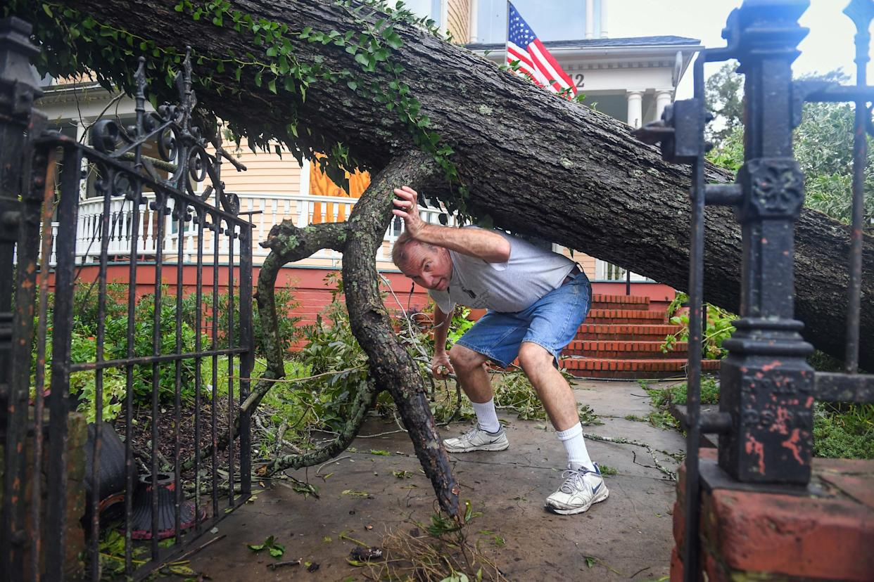 Doug Erickson begins the task of cleaning the large fallen pecan tree in front of the CW Worth House in Wilmington.