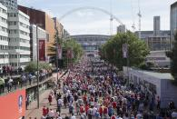 FILE - In this Saturday, May 27, 2017 file photo, people walk towards Wembley Stadium ahead of the FA Cup final soccer match between Arsenal and Chelsea, in London. The British government faced accusations of mixed messaging Wednesday June 23, 2021, that could threaten its plan to fully lift lockdown restrictions in England next month after it decided to allow more than 60,000 people inside Wembley Stadium for the latter stages of soccer's European Championship. (AP Photo/Tim Ireland, File)