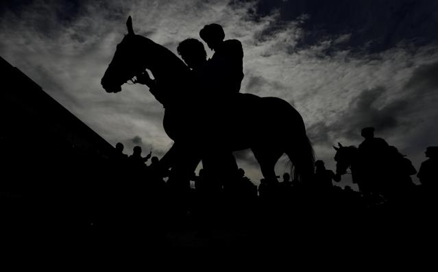 Horse Racing - Cheltenham Festival - Cheltenham Racecourse, Cheltenham, Britain - March 15, 2018 Silhouette of jockeys and horses before the 14:10 Pertemps Network Final Handicap Hurdle Action Images via Reuters/Andrew Boyers