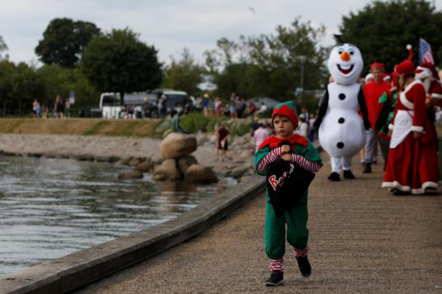 <p>A child dressed as an elf walks along the waterfront during an event in the World Santa Claus Congress, an annual event held every summer in Copenhagen, Denmark, July 23, 2018. (Photo: Andrew Kelly/Reuters) </p>