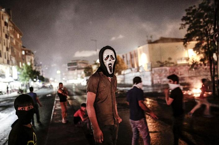 Masked protesters stand on the street in Istanbul on July 22, 2015, two days after a suicide bomb attack killed 32 people in the southern Turkish town of Suruc (AFP Photo/Yasin Akgul)