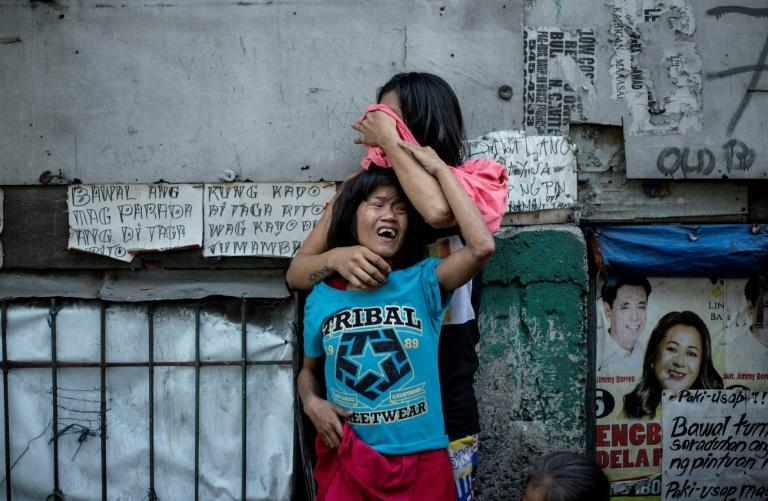 Two Filipinos mourn the death of a relative, a suspected drug dealer gunned down by unidentified assailants in Manila earlier in March as part of President Duterte's deadly drug war