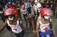 Red Cross workers carry a man on a stretcher in Mandalay, Myanmar on Saturday, Feb. 20, 2021. Security forces in Myanmar ratcheted up their pressure against anti-coup protesters Saturday, using water cannons, tear gas, slingshots and rubber bullets against demonstrators and striking dock workers in Mandalay, the nation's second-largest city. (AP Photos)