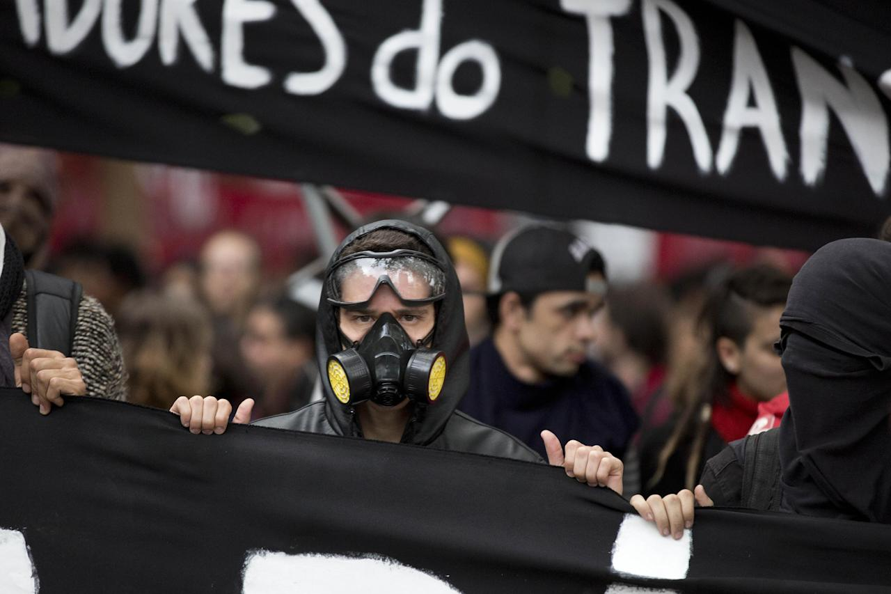 Masked protesters carry a banner while marching in Sao Paulo, Brazil, Thursday, June 19, 2014. The protest in Sao Paulo, Brazil's biggest city that is hosting a World Cup match, was called by the Free Fare movement, the group that was behind the first protests last year that sparked roiling anti-government demonstrations across Brazil. (AP Photo/Eduardo Verdugo)