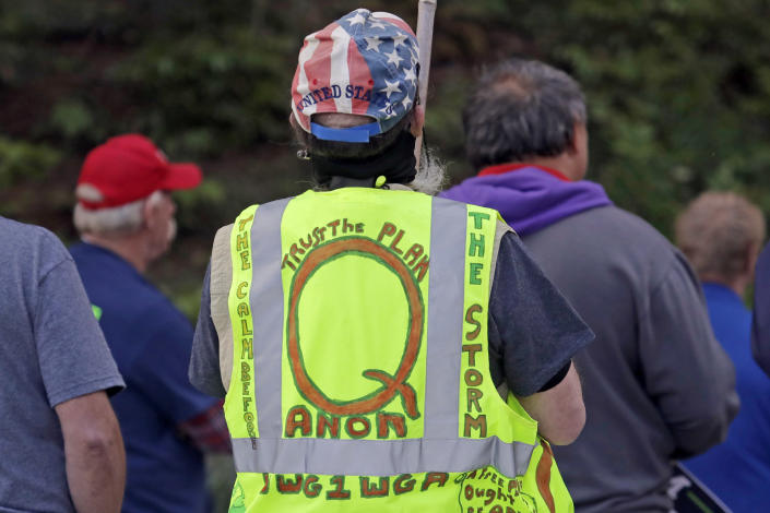 FILE - In this May 14, 2020, file photo, a person wears a vest supporting QAnon at a protest rally in Olympia, Wash., against Gov. Jay Inslee and Washington state stay-at-home orders made in efforts to prevent the spread of the coronavirus. President Joe Biden's inauguration has sown a mixture of anger, confusion and disappointment among believers in the baseless QAnon conspiracy theory. (AP Photo/Ted S. Warren, File)
