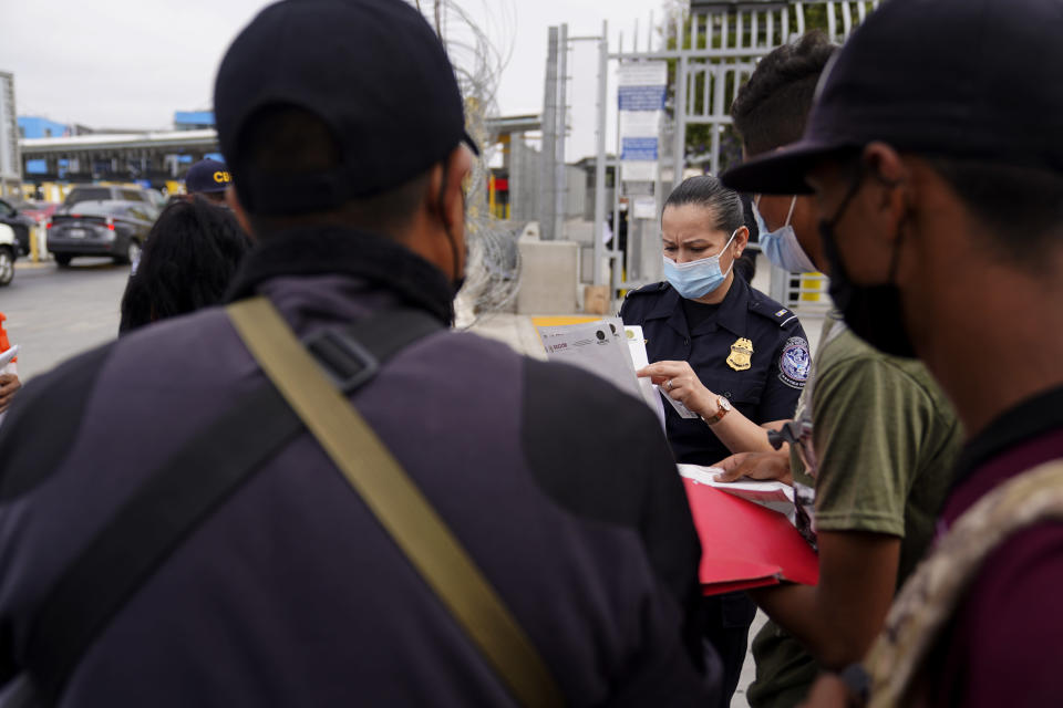 A United States Customs and Border Protection officer examines paperwork of migrants waiting to cross into the United States to begin the asylum process Monday, July 5, 2021, in Tijuana, Mexico. Dozens of people are allowed into the U.S. twice a day at a San Diego border crossing, part of a system that the Biden administration cobbled together to start opening back up the asylum system in the U.S. Immigration advocates have been tasked with choosing which migrants can apply for a limited number of slots to claim humanitarian protection. (AP Photo/Gregory Bull)