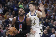 Los Angeles Clippers' Paul George (13) goes to the basket against Indiana Pacers' Doug McDermott (20) during the first half of an NBA basketball game, Monday, Dec. 9, 2019, in Indianapolis. (AP Photo/Darron Cummings)