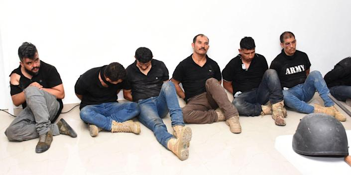 Six men in black shirts and handcuffs sitting in a line.