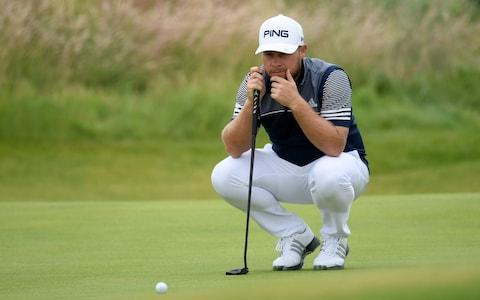 Tyrrell Hatton of England lines up his putt on the 13th green during the second round of the 148th Open Championship - Credit: GETTY IMAGES
