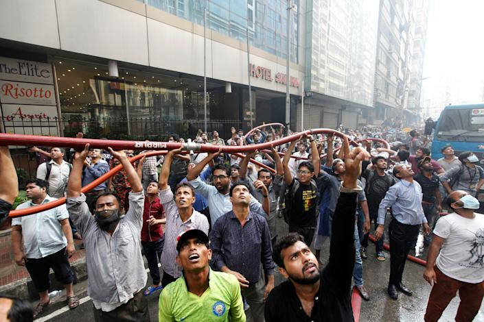 Locals help firefighters work to douse a fire in a multi-storied office building in Dhaka, Bangladesh,  March 28, 2019. (AP Photo/Mahmud Hossain Opu)