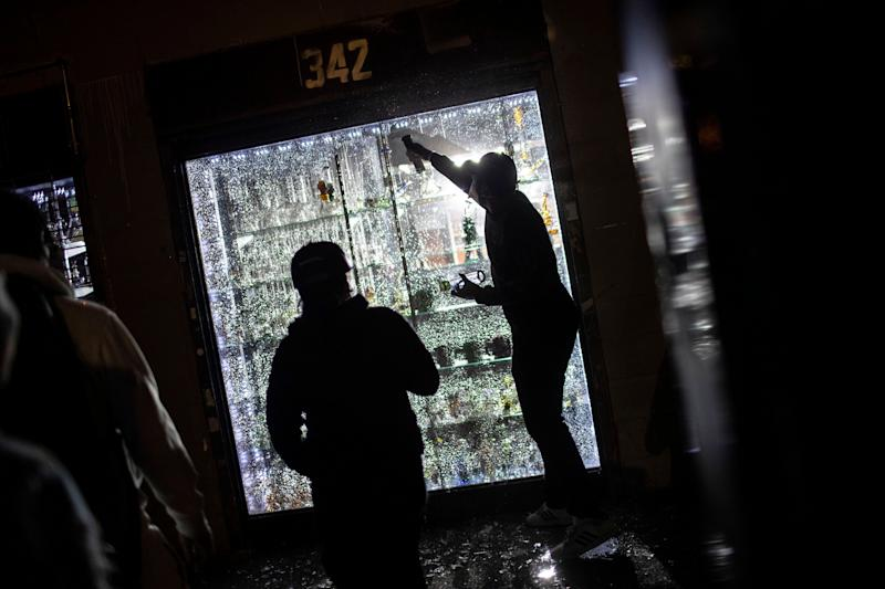 People break into a smoke shop on Monday, June 1, 2020, in New York. Protests were held throughout the city over the death of George Floyd, a black man in police custody in Minneapolis who died after being restrained by police officers on Memorial Day. (AP Photo/Wong Maye-E)