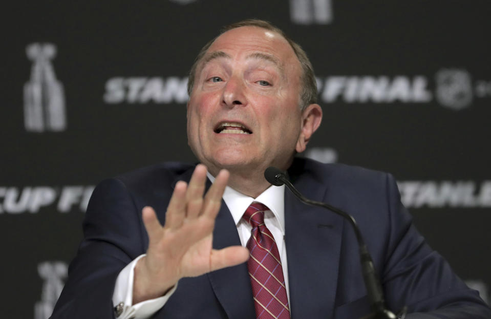 FILE - In this May 27, 2019, file photo, NHL Commissioner Gary Bettman speaks to the media before Game 1 of the NHL hockey Stanley Cup Final between the St. Louis Blues and the Boston Bruins in Boston. The most aggressive timetable, a person familiar with discussions told The Associated Press, would have players returning to their home rinks as early as May 15, followed by a training camp and possible exhibition games in June. Bettman emphasized no decisions have been made and cautioned government and medical officials will ultimately make the call on when sports can return. (AP Photo/Charles Krupa, File)