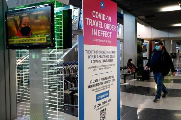 A traveller walks through Terminal 3 as a COVID-19 travel order sign is displayed at O'Hare International Airport in Chicago, Sunday, Nov. 29, 2020.