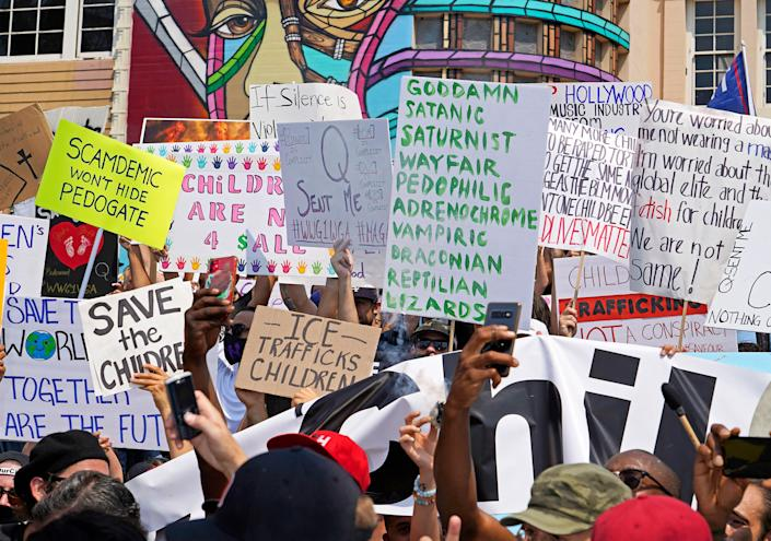 """Signs showing various conspiracy theories at a Save Our Children rally in Los Angeles, Aug. 22, 2020. <span class=""""copyright"""">Jamie Lee Curtis Taete</span>"""
