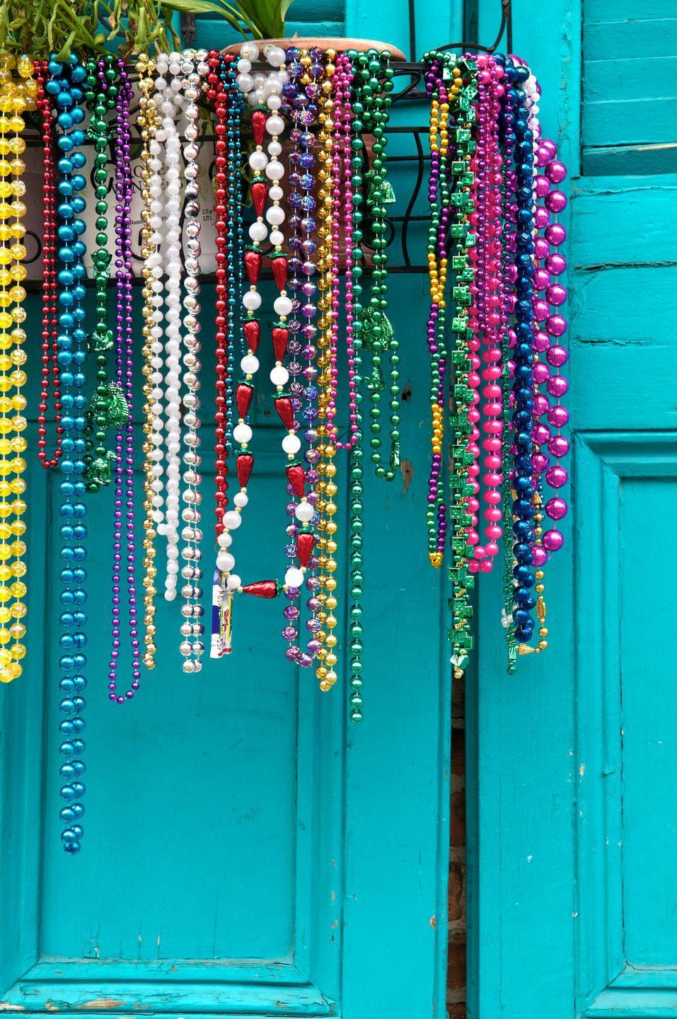 """<p>Throws are the baubles that krewes toss to the crowd from their parade floats (and in more recent years, that those partying on the French Quarter balconies gift to passersby). They include doubloons, the <a href=""""https://www.whereyat.com/the-wild-world-of-doubloon-collecting"""" rel=""""nofollow noopener"""" target=""""_blank"""" data-ylk=""""slk:collectible coins"""" class=""""link rapid-noclick-resp"""">collectible coins</a> krewes give out, and those infamous plastic beads. According to <em><a href=""""https://time.com/5144265/mardi-gras-traditions-history/"""" rel=""""nofollow noopener"""" target=""""_blank"""" data-ylk=""""slk:Time"""" class=""""link rapid-noclick-resp"""">Time</a></em>, these traditions likely began in the late 1800s, when carnival kings would gift their """"subjects"""" with the trinkets.</p>"""