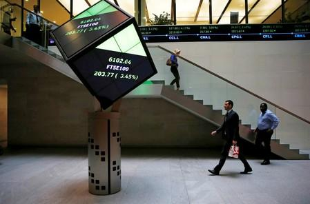 People walk through the lobby of the London Stock Exchange in London