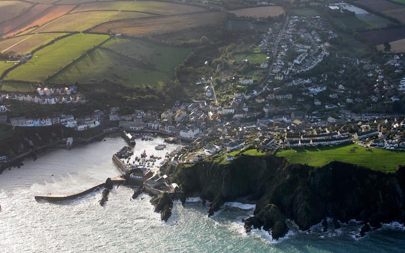 Cornwall boasts its own picturesque coastline, including the fishing port and town of Mevagissey Near St Austell - Credit: Getty Images