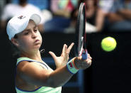 Australia's Ashleigh Barty makes a forehand return to Slovenia's Polona Hercog during their second round singles match at the Australian Open tennis championship in Melbourne, Australia, Wednesday, Jan. 22, 2020. (AP Photo/Dita Alangkara)