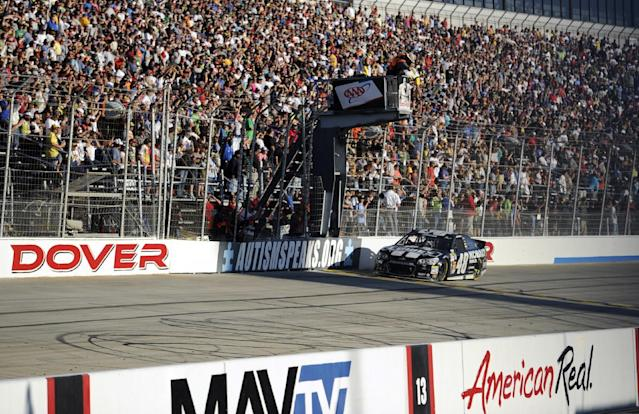 Jimmie Johnson takes the checkered flag to win a NASCAR Sprint Cup Series auto race on Sunday, Sept. 29, 2013, at Dover International Speedway in Dover, Del. (AP Photo/Nick Wass)