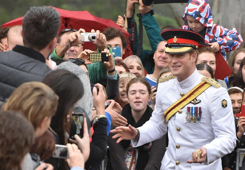 Britain's Prince Harry (C) braves the rain to shake hands with onlookers after laying a wreath at the Australian War Memorial in Canberra, on April 6, 2015 (AFP Photo/Mark Graham)