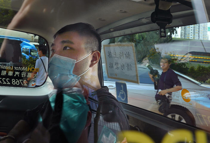 """FILE - In this July 6, 2020, file photo, Tong Ying-kit arrives at a court in a police van in Hong Kong. Hong Kong High Court will deliver verdict Tuesday afternoon, July 27, 2021 for the first person charged under Hong Kong's National Security Law. Tong was arrested in July 2020 after driving his motorbike into a group of police officers while carrying a flag bearing the protest slogan """"Liberate Hong Kong."""" He was charged with inciting separatism and terrorism. (AP Photo/Vincent Yu,File)"""