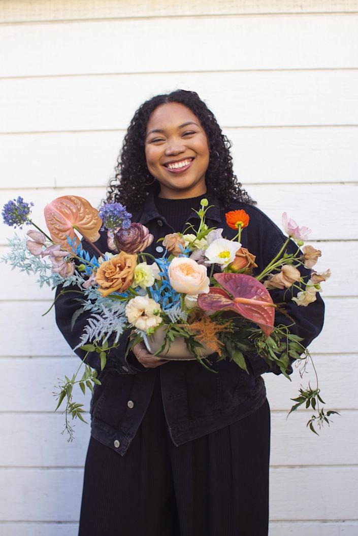 Mallory Browne holds a floral arrangement.