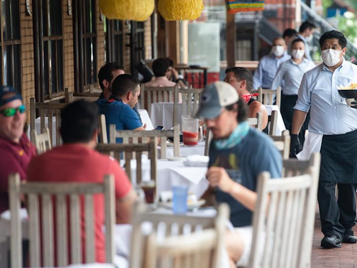 """A waiter wearing a mask and gloves delivers food to a table to customers seated at an outdoor patio at a Mexican restaurant in Washington, DC, May 29, 2020. <p class=""""copyright"""">SAUL LOEB/AFP/Getty Images</p>"""