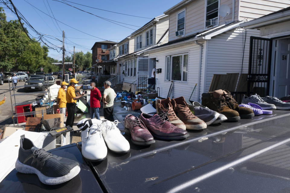 FILE - In this Sept. 3, 2021, file photo, shoes dry on the roof of a car in the Queens borough of New York. Floodwaters from the remnants of Hurricane Ida have long receded but Northeast residents still in the throes of recovery are being hit with another unexpected blow: Thousands of families without flood insurance are now swamped with financial losses after runoff from the fierce storm submerged basements, cracked foundations and destroyed valuable belongings. (AP Photo/Mark Lennihan, File)