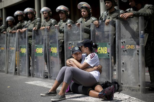 <p>Women embrace as they sit in front of a line of the National Bolivarian Guard outside the Palace of Justice in Caracas, Venezuela, Feb. 19, 2014. After a dramatic surrender and a night in jail, Venezuelan opposition leader Leopoldo Lopez was due in court to learn what charges he faced for allegedly provoking violence during protests against the socialist government in the divided nation. (Photo: Rodrigo Abd/AP) </p>