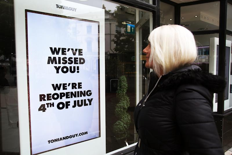 A general view of a woman reading a window sign at the Toni & Guy hairdressing salon in Worthing, Sussex, ahead of its reopening on Saturday 4th July as the UK continues to introduce measures to gradually bring the country out of the coronavirus lockdown.