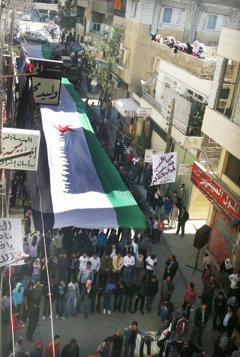In this image provided by the Local Coordination Committees in Syria and accessed on Friday, April 13, 2012, anti-regime protesters carry a large Syrian revolutionary flag during a demonstration in Damascus, Syria. Syrian troops shelled residential neighborhoods dominated by rebels in the central city of Homs Sunday, activists said, hours before the first batch of United Nations observers were to arrive in Damascus to shore up a shaky truce.(AP Photo/Local Coordination Committees in Syria) THE ASSOCIATED PRESS IS UNABLE TO INDEPENDENTLY VERIFY THE AUTHENTICITY, CONTENT, LOCATION OR DATE OF THIS HANDOUT PHOTO