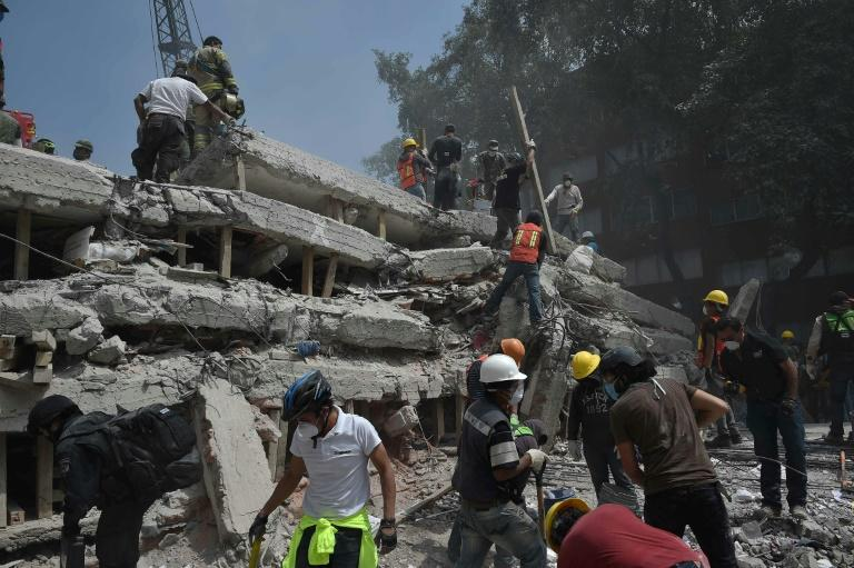 Rescuers and volunteers search for survivors amid the rubble and debris of a multistory building flattened by the 7.1-magnitude quake