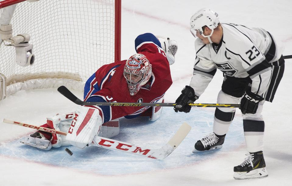 Montreal Canadiens goaltender Carey Price makes a save against the Los Angeles Kings as Kings' Dustin Brown looks for the rebound during the second period of an NHL hockey game, Friday, Dec. 12, 2014 in Montreal. (AP Photo/Canadian Press, Graham Hughes)