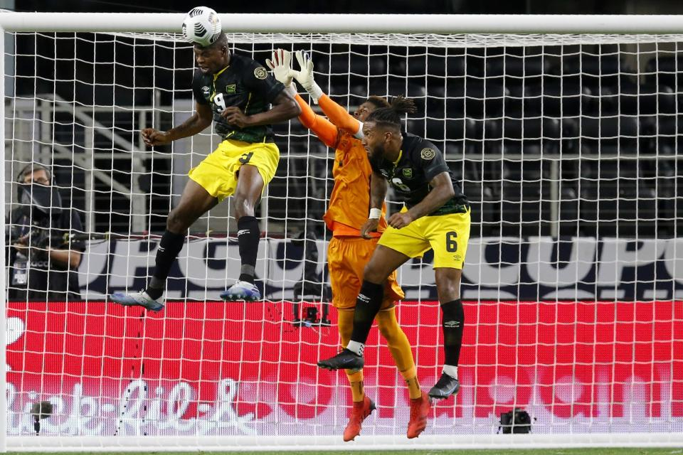 Jamaica forward Cory Burke (9) and defender Liam Moore (6) help goalkeeper Andre Blake (1) against a shot by the United States in the first half of a CONCACAF Gold Cup quarterfinals soccer match, Sunday, July 25, 2021, in Arlington, Texas. (AP Photo/Brandon Wade)