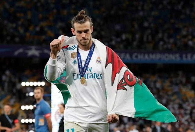 Soccer Football - Champions League Final - Real Madrid v Liverpool - NSC Olympic Stadium, Kiev, Ukraine - May 26, 2018 Real Madrid's Gareth Bale celebrates with a Wales flag and medal after winning the Champions League REUTERS/Andrew Boyers