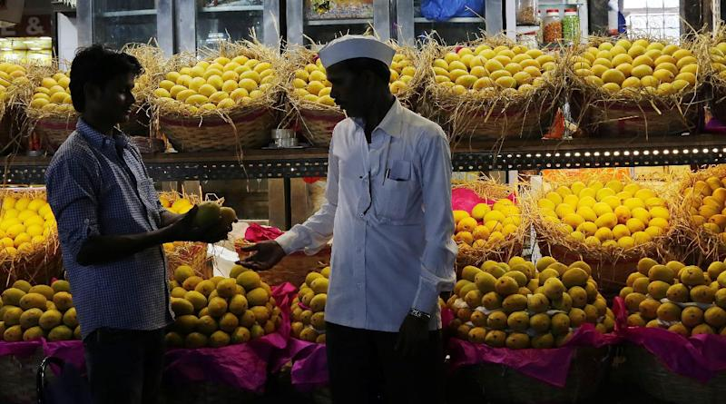 In this Tuesday, May 6, 2014 photo, an Indian vendor, left, shows samples of Alphonso mangoes to a customer at a whole sale market in Mumbai, India. Starting May 1, the EU banned imports of Indian mangoes including the Alphonso, considered the king of all the mango varieties available in South Asia. The ban was implemented because a large number of shipments were contaminated with fruit flies. (AP Photo/Rajanish Kakade)