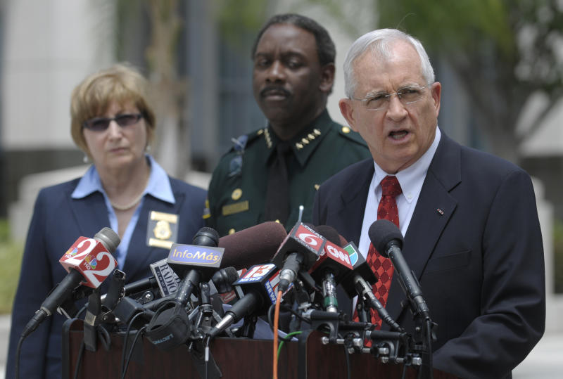 Florida State Attorney Lawson Lamar, right, announces charges against 13 people in the hazing death of Florida A&M University drum major Robert Champion during a news conference in Orlando, Fla., Wednesday, May 2, 2012. The charges were announced more than five months after Champion, 26, died aboard a chartered bus parked outside an Orlando hotel following a performance against a rival school. Standing next to Lamar are Florida Department of Law Enforcement Special Agent Joyce Dawley, left, and Orange County Sheriff Jerry Demings.  (AP Photo/Phelan M. Ebenhack)