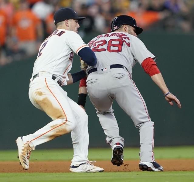 Boston Red Sox's J.D. Martinez (28) is tagged out by Houston Astros third baseman Alex Bregman (2) after being caught in a rundown during the seventh inning of a baseball game Saturday, May 25, 2019, in Houston. (AP Photo/David J. Phillip)