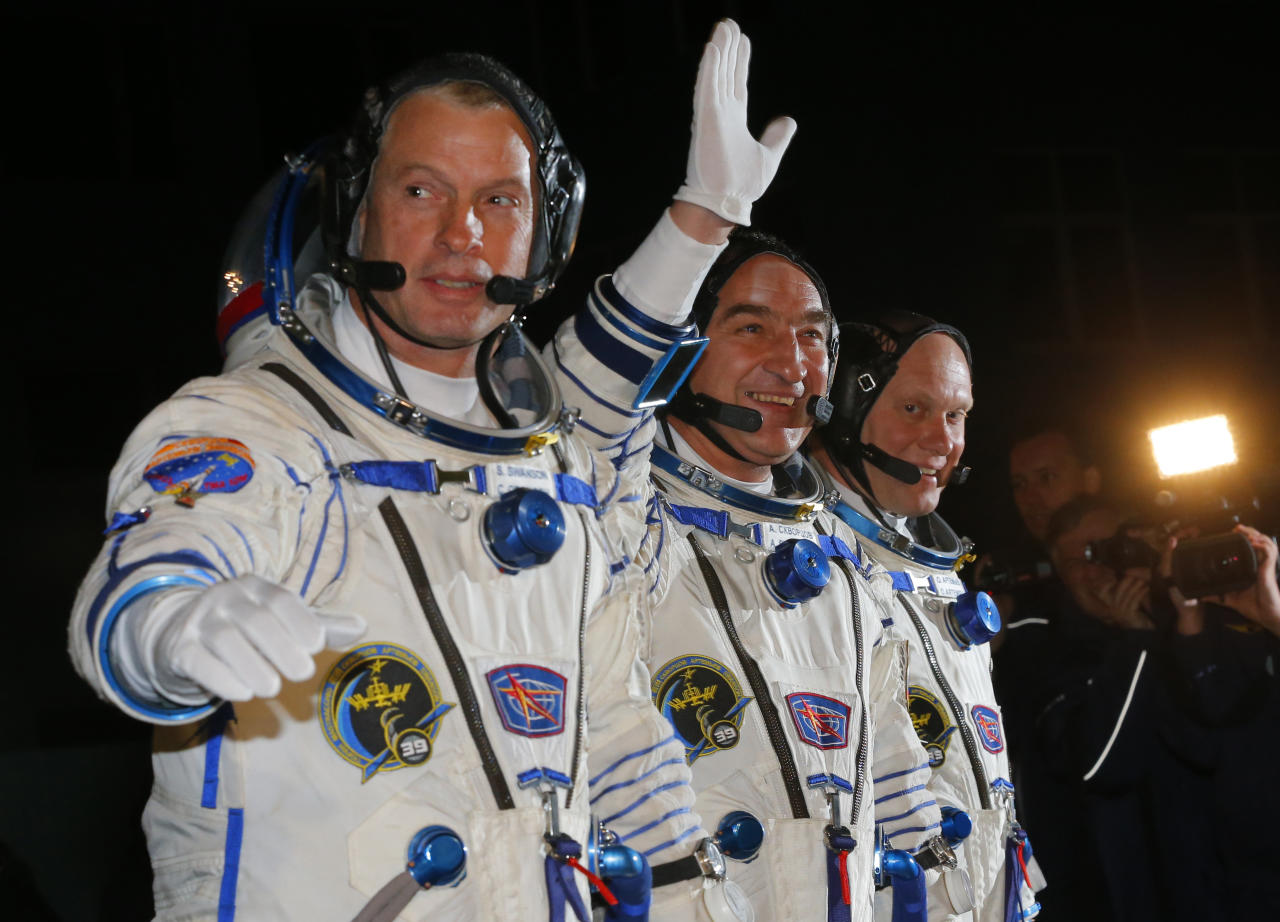 U.S. astronaut Steven Swanson, left, Russian cosmonauts Alexander Skvortsov, center, and Oleg Artemyev, crew members of the mission to the International Space Station (ISS) walk prior the launch of Soyuz-FG rocket at the Russian leased Baikonur cosmodrome, Kazakhstan, Wednesday, March 26, 2014. (AP Photo/Dmitry Lovetsky, Pool)
