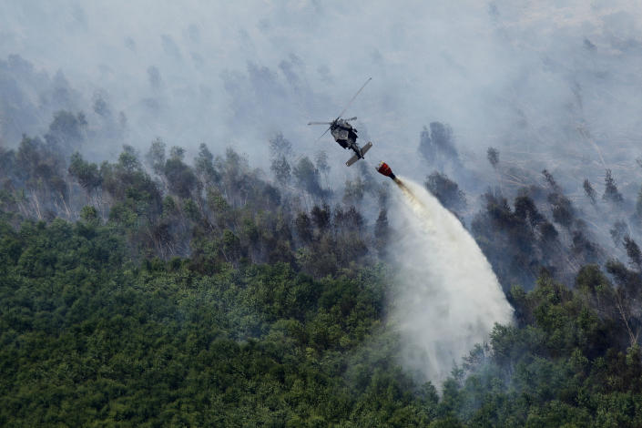 A Louisiana National Guard helicopter dumps water on a burning marsh fire in Eastern New Orleans, Wednesday, Aug. 31, 2011. Haze from the fire was reported as far west as the Baton Rouge metro area, the National Weather Service said. It expanded its smoke alert from New Orleans and six suburban parishes to 23 parishes, including towns 100 miles from New Orleans. (AP Photo/Gerald Herbert)
