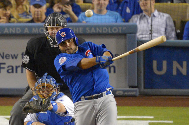 Chicago Cubs' Dioner Navarro, right, hits an RBI single as Los Angeles Dodgers catcher A.J. Ellis, lower left, looks on along with home plate umpire Gary Cederstrom during the third inning of a baseball game, Tuesday, Aug. 27, 2013, in Los Angeles. (AP Photo/Mark J. Terrill)