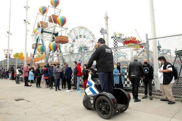 Guests line up on the first day of the Coney Island parks reopening, during the COVID-19 pandemic, in the Coney Island neighborhood of Brooklyn, New York on April 9, 2021.