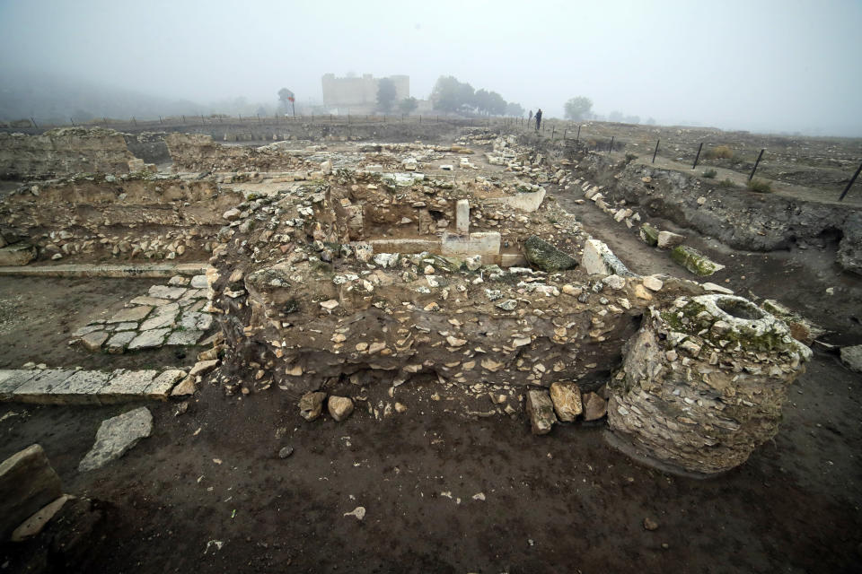 FILE - In this file photo taken on Wednesday, Nov. 18, 2020, a journalist looks at a ruined Tigranakert, Armenian city dating back to the Hellenistic period, in the separatist region of Nagorno-Karabakh. In marked contrast to the thorough destruction of Agdam city, ethnic Armenians have taken assiduous care of one of their major historical sites in the province. The foundations of ancient Tigranakert, some two millennia old, have undergone archaeological excavation and some of what has been found placed in an 18th century fortress. (AP Photo/Sergei Grits, file)