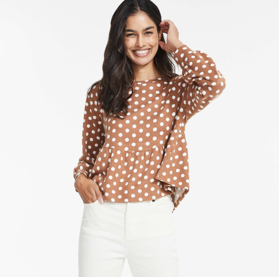model in brown and white polka dot top and white jeans