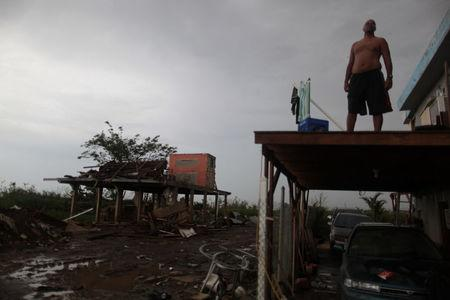 A man stands on what is left of the balcony of his home and near another destroyed house, after the island was hit by Hurricane Maria in Toa Baja, Puerto Rico October 16, 2017. REUTERS/Alvin Baez