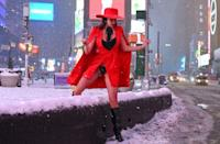 A woman climbs over a snow-covered wall in Time Square during a winter storm on February 1, 2021 in New York City