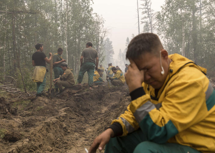 FILE - In this Sunday, July 18, 2021 file photo, employees of the Yakutlesresurs rest as they dig a moat to stop a forest fire outside Magaras village 87 km. (61 miles) west of Yakustk, the capital of the republic of Sakha also known as Yakutia, Russia Far East. Each year, thousands of wildfires engulf wide swathes of Russia, destroying forests and shrouding broad territories in acrid smoke. This summer has seen particularly massive fires in Yakutia in northeastern Siberia following unprecedented heat. (AP Photo/Alexey Vasilyev, File)
