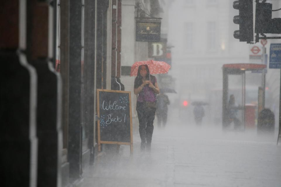 A woman wearing PPE (personal protective equipment), of a face mask or covering as a precautionary measure against COVID-19, shelters under an umbrella they are caught in a downpour of rain on Oxford Street in London on June 17, 2020, as lockdown restrictions imposed to stem the spread of the novel coronavirus continue to be relaxed. - Britain's annual inflation rate slid to 0.5 percent in May, the lowest level in four years, as the country's coronavirus lockdown dampens prices, official data showed Wednesday. (Photo by Tolga AKMEN / AFP) (Photo by TOLGA AKMEN/AFP via Getty Images)