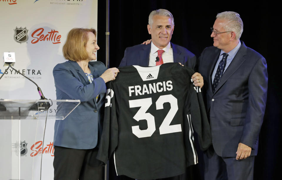 Ron Francis, center, is presented with a hockey jersey by Seattle Mayor Jenny Durkan, left, as Seattle Hockey Partners CEO Tod Leiweke looks on Thursday, July 18, 2019, in Seattle, as Francis is introduced as the first general manager for Seattle's yet-to-be-named NHL expansion team. Francis, a Hall of Famer and a two-time Stanley Cup winner, will have complete control of operations under Leiweke when the team debuts in 2021. (AP Photo/Ted S. Warren)